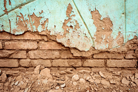 Grunge style background of a red brick wall crumbling with age and a green painted surface