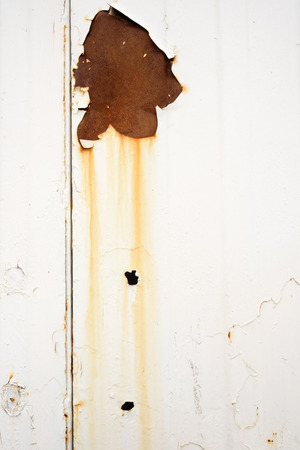 decomposing: Old rust spot and holes in orange with bleed runs on a white metal surface that has a grimy and grunge look Stock Photo