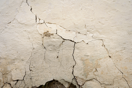 fissures: Craked white painted wall with large fissures on the mottled shaded plaster surface