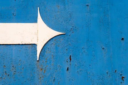 entropy: Single white metal arrowhead on a rusty dark blue metal background. Copy space area using the arrow for text and design overlays. Stock Photo