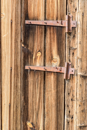 hinges: Old faded and weathered wood with two rusted metal hinges. Copy space area for design text. Stock Photo