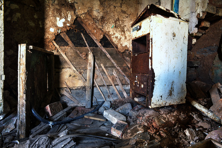 grimy: Old forgotten and abandoned home interior in a derelict decaying state with grimy floors and ripped wallpaper and a disused fridge.
