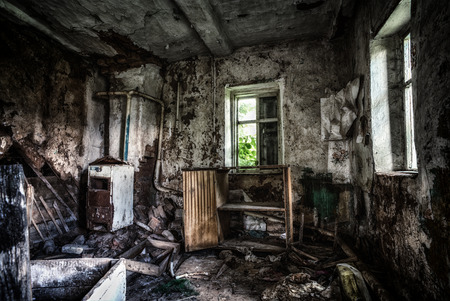 grimy: Old forgotten and abandoned home interior in a derelict decaying state with grimy floors and ripped wallpaper.