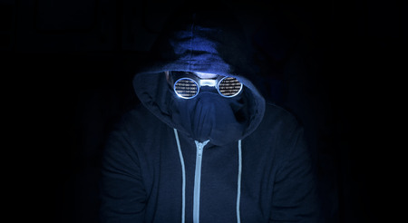Hooded computer criminal hacker sits in a dark room wearing goggles to conceal his identity as he commits crimes on the internet.