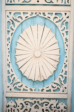 hand carved: Hand carved wood detail with ornate details painted in white and blue paint