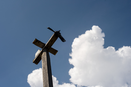 Single wooden airplane weathervane set against a blue sky with a large white cloud. Stock Photo