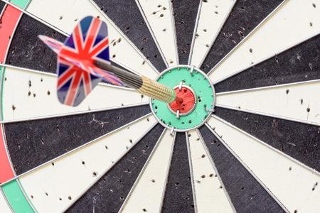 English Union Jack flag metal dart that has hit the red bullseye of a dartboard.