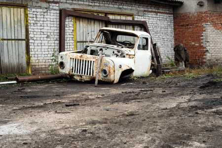 scrapped: Broken and scrapped white lorry truck cabin used for salvaging parts rests outside a brick garage.