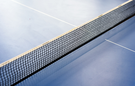 Diagonal table tennis net on a blue tabletennis table. Copy space area for sport themed designs and backgrounds Stock Photo