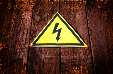 or electrocution: Yellow shaped electricity warning sign with a black electric bolt on a dark aged wood grunge style background.