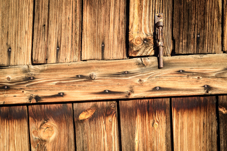 fading: Rusty metal hinge on aged faded wood in brown. Vertical composition of fading timber and a door entrance opening.