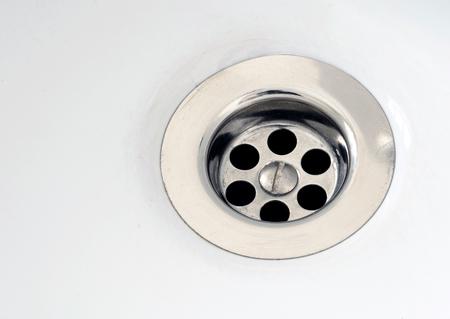 sink drain: Single silver kitchen or bath sink plughole set in a white ceramic bathroom Stock Photo