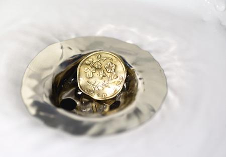 libra esterlina: Libra británica sola moneda descansando en un plughole de plata con gotas de agua sobre la moneda y la superficie de cerámica blanca Foto de archivo