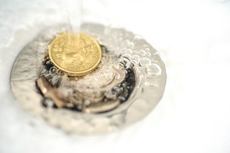 wasting away: British money including a one pound coin stuck in a sink drain plughole as water flows over the coins.