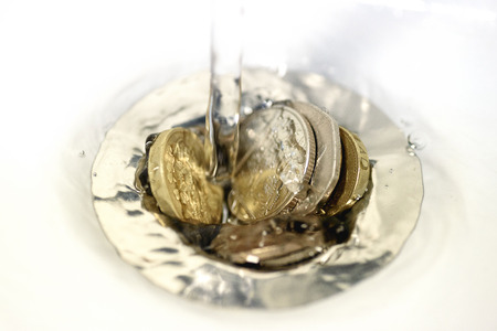 British money including a one pound coin stuck in a sink drain plughole as water flows over the coins.