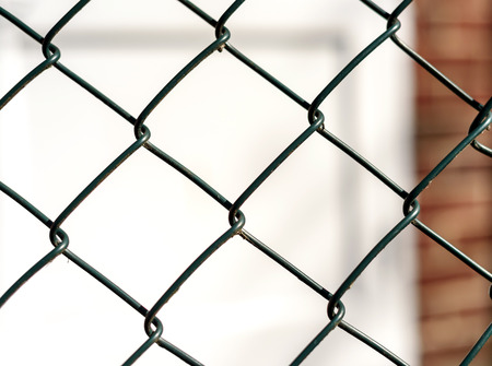 jail: Single Chain mesh link fence with a defocused white door in the background