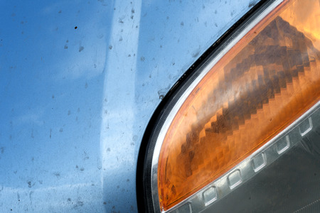 Silver blue car headlamps with indicator lights on an unknown vehicle with dust and grime from being used on the road Reklamní fotografie