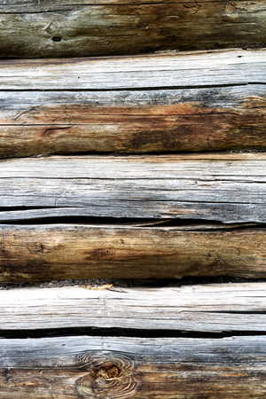 Old dry timber from an old log house. The wooden construction shows signs of age and weathering