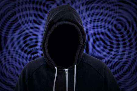 Unknown faceless hooded cyber criminal with binary code in the background