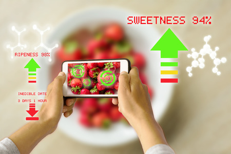 Woman holding a smart device uses reality augmentation to examine the ripeness of a bowl of strawberries Stock Photo