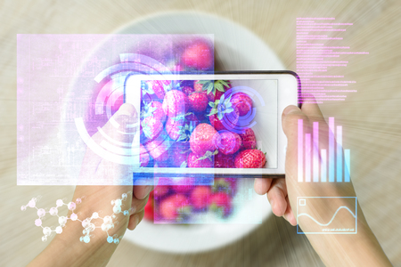 Woman holding a smart device uses reality augmentation to examine a pile of strawberries
