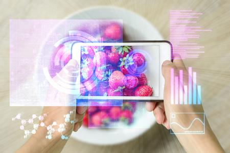 スマート デバイスを保持している女性現実増強を使用してイチゴの山を調べます 写真素材