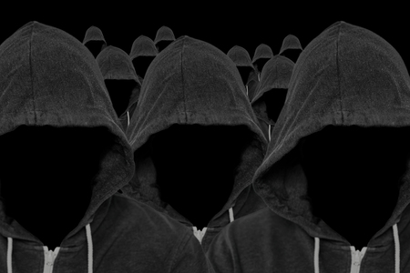 Mass of faceless mysterious and unknown hooded people with unseen faces and a black background