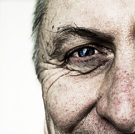 Closeup of an aged mans face and eye with intentional grain and grunge style applied