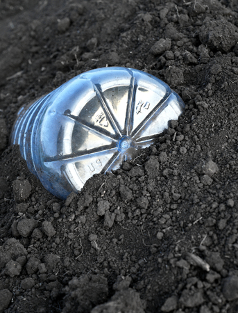 5 litre plastic PET bottle discarded ad left in brown soil with copyspace area for recycling and environmental issue designs Stock Photo