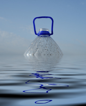 Junk PET 5 litre plastic drinking bottle floating in the sea partly submerged beneath the surface