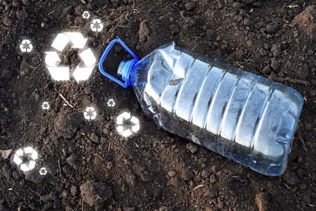 Emptied PET 5 plastic gallon drinking container sunken into brown earth with recycle signs scattered on the soil Stock Photo