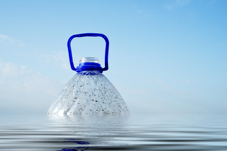 Plastic PET bottle floating in sea water partly submerged Stock Photo