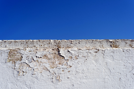 White cement wall with flaking paint and a blue summer sky with copy space area for construction ideas