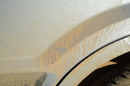 Mud and dirt covered car wheel arch of a silver paintwork vehicle Stock Photo