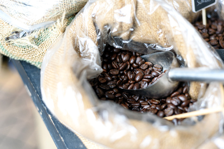 Close-up image of coffee beans in a hessian sack with a silver spoon on display at a farmer's market