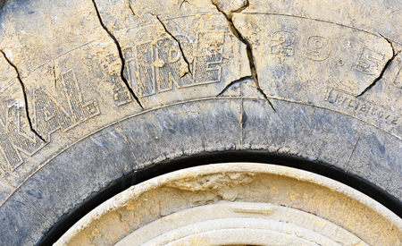Cracked work tires of a large industrial earthmoving machine with yellow rims and clay mud caked rips and tears Stock Photo