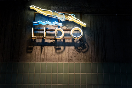 Lido swimming pool sign with a woman diving into wavy water in a neon light style