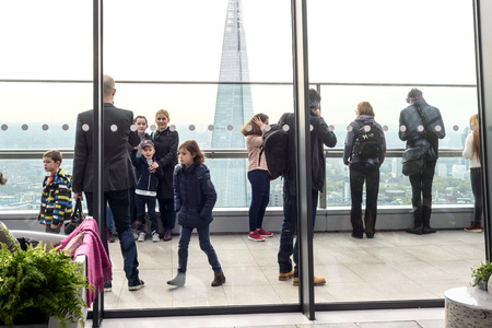 People inside viewing the free Sky Garden cafe on the 35th floor of 20 Fenchurch Street in London with the shard in the background