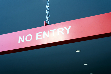 White text no entry sign on a red background hanging from a chain