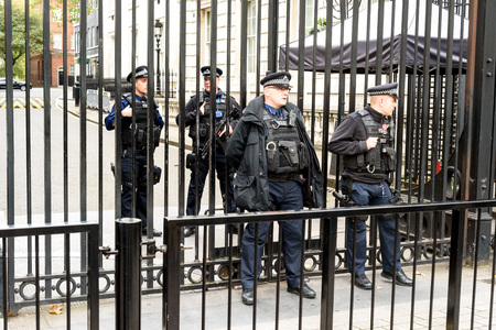 Armed police officers outside the gates of 10 Downing Street in London providing protection against the famous London government landmark