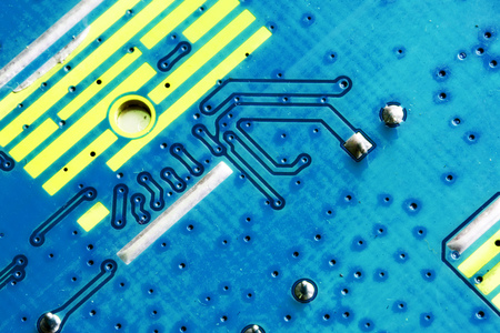 Electronic PCB printed circuit board in macro close-up with transistors circuitry and electric hardware elements including computer chip with copy space for computer industry designs and ideas Stock Photo