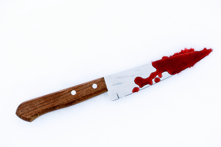 Sharp metal kitchen knife edge used as a violent murder weapon with blood drops on a white snow background. Blade covered in violence with copy space area for domestic crime criminal designs