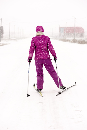 Young woman dressed in purple snow clothes and suit cross country skiing on a village road in a strong snow blizzard in a wintry snow swept scene and cold temperatures Stock Photo