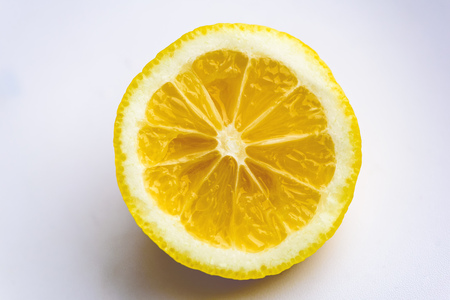 Slice of a bright yellow lemon on a white background with close up of the citrus textures on the interior of the bitter fruit