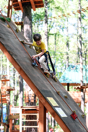 UFA, RUSSIA, 23RD MAY 2018 - A young boy descends down a steep outdoor climbing ramp as part of his outdoor activity at an adventure park in Russia in 2018 新聞圖片