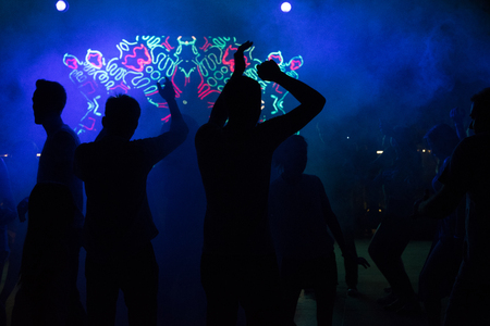 People dance at a nightclub at night in silhouette with different color lights and digital effects