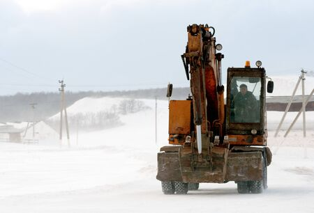 RAEVKA, RUSSIA - FEBRUARY 22, 2019: An earthmover crane moves along a snow road in Raevka during the witner months. These machines are used to clear snow from roads.