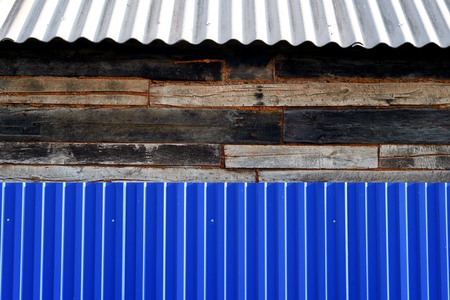 House exterior of a blue metal fence and old aged wooden walls with a grey asbestos style roof Zdjęcie Seryjne