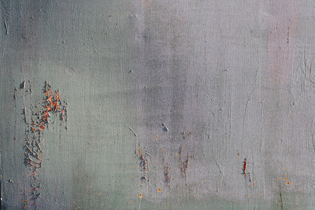 Scratched paint on a wooden plywood background with damage to the green grey paint exterior