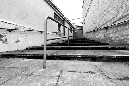 Steps lead to a metal door of a building exterior shot in black and white